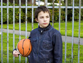 Young basketball player holding ball against iron fence at the p — Foto de Stock