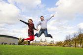 Exterior casal feliz pulando na museumplein, amsterdam — Fotografia Stock