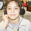 Portrait of a sweet young boy listening to music on headphones — Stock Photo #36531989