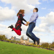 Outdoor happy couple jumping in Museumplein, Amsterdam — Stockfoto
