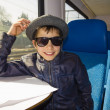 Handsome boy with sunglasses rides on a train reading from the paper — Stock Photo #36785693