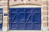 Ancient blue wooden door  background at house number 73 — Stock Photo