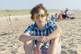 Teenage boy sitting on the beach — Foto Stock
