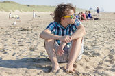 Portrait of  teenage guy siting on sand — Foto de Stock
