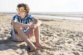 Nastoletni chłopiec siedzi na plaży — Zdjęcie stockowe