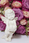 Statue of an angel with heart on a background of flowers — Stock Photo