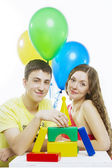 Happy young couple play with toys on white background — Stock Photo