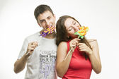 Happy young couple with colorful lollipops on white background — Stock Photo