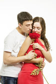 Happiness young love couple with a flower on a white background — Stock Photo