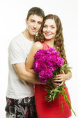 Beautiful young love couple on a white background with a bouquet of flowers — Stock Photo