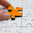 Hands placing piece of a Puzzle — Stock Photo #22413847