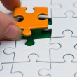 Stock Photo: Hands placing piece of a Puzzle