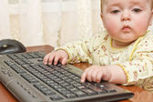Kid gets acquainted with a computer keyboard — Stock Photo