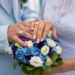 Hands with wedding rings and beautiful blue and white fresh flow — Stock Photo