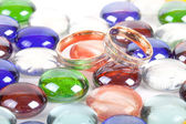 Two wedding rings on a colorful marbles — Foto Stock