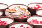 Two wedding rings on chocolates with raspberries — Stock Photo