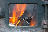 Wood and the fire in the furnace with flying sparks — Stock Photo
