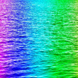Rainbow colored water waves in ocean — Stock Photo