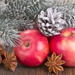 Christmas red apples, snow-covered pine cone and fir branches — Stock Photo