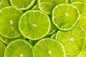 Grüner hintergrund mit kalk-slices — Stockfoto
