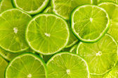 Zelené pozadí s plátky limetky — Stock fotografie