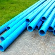 Stock Photo: Harmless polyethylene water pipes on green grass