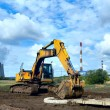 Stock Photo: Excavator against the dark blue sky with clouds and industrial pipes