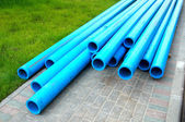 Harmless polyethylene water pipes on a green grass — Stock Photo