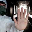 The man in protective overalls and respirator shows a sign biological or radioactive danger — Stock Photo #17500199
