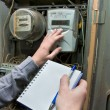 Stock Photo: Hands write down water meter registration