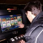 Постер, плакат: Man playing at the slot machines