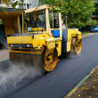 Road repair, compactor lays asphalt. - Stock Photo