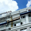 Workers repair a building facade - Stock Photo
