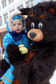 Barn i händerna på man klädd som en björn — Stockfoto