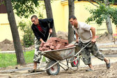 Men carry stones in a wheelbarrow — 图库照片