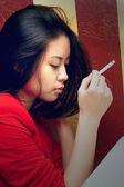 Asian girl thoughtfully sits with a cigarette — Stockfoto