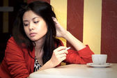 Asian girl with a cigarette in cafe — Stock Photo