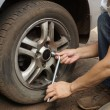 Stockfoto: Man changes the wheel of the car