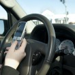 Stock Photo: Hand of teen texting while driving