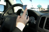 Hand of a teen texting while driving — Stock Photo