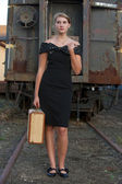Woman with suitcase on railroad tracks — Stock Photo