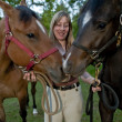 Pretty woman holding two horses — Stock Photo