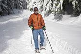 Senior man snowshoeing — Stock Photo