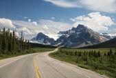 Carretera pasando por debajo de las montañas — Foto de Stock