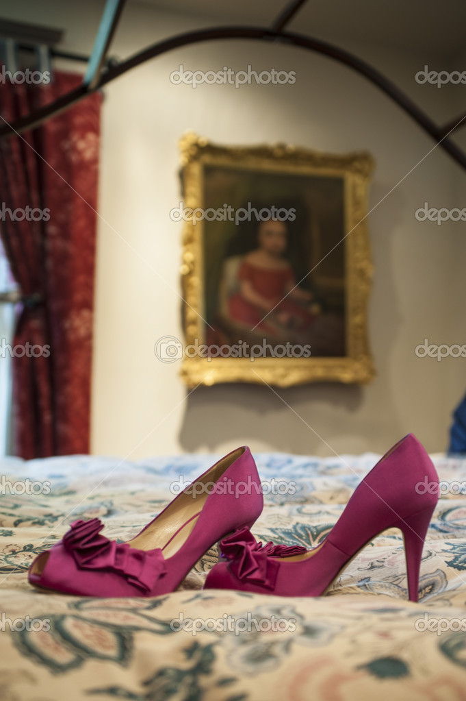 Sexy red high heels resting on an antique bed — Stock Photo #21544529