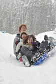 Teens sledding on a saucer — Stock Photo