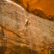 Man rappelling down cliff in desert - Stock Photo