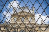 Louvre Palace building seen through pyramid — Stock Photo
