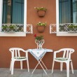 Table and chairs outside a house, Burano, Italy - Stock Photo