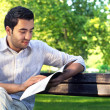 Young handsome guy reading book in the park — Stock Photo